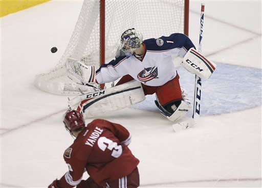 Columbus Blue Jackets goalie Steve Mason deflects a shot on goal by Phoenix Coyotes' Keith Yandle (3) during the second period of an NHL hockey game, Saturday, Feb. 16, 2013, in Glendale, Ariz. (AP Photo/Matt York)
