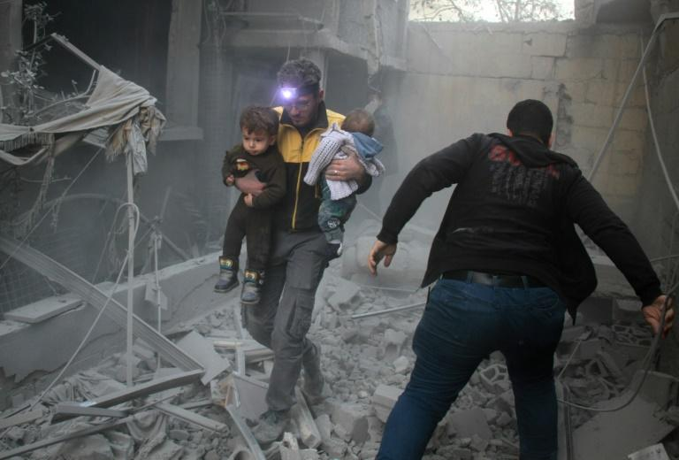 A Syrian man carries two children in the rubble of buildings following regime air strikes on the rebel-held besieged town of Douma in the eastern Ghouta region, on the outskirts of the capital Damascus