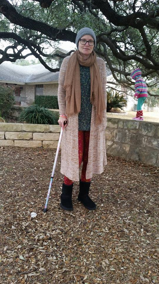 woman wearing several jackets and a robe standing outside with a cane