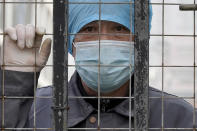 A worker wearing a face mask watches from inside a hospital across the Wuhan Center for Disease Control and Prevention after the World Health Organization team arrive to make a field visit in Wuhan in central China's Hubei province on Monday, Feb. 1, 2021. (AP Photo/Ng Han Guan)