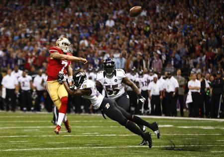 49ers quarterback Kaepernick throws under pressure from Ravens Reed during the NFL Super Bowl XLVII football game in New Orleans