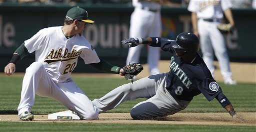 Seattle Mariners' Carlos Triunfel, right, slides safe at third base beneath the tag of Oakland Athletics third baseman Josh Donaldson in the fifth inning of a baseball game Saturday, Sept. 29, 2012, in Oakland, Calif. Triunfel advanced to third on a sacrifice fly hit by Franklin Gutierrez. (AP Photo/Ben Margot)