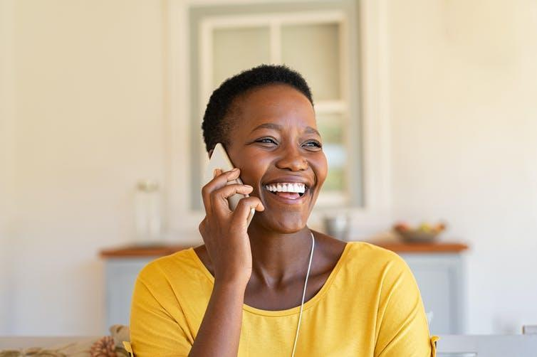 A woman smiling on the phone.