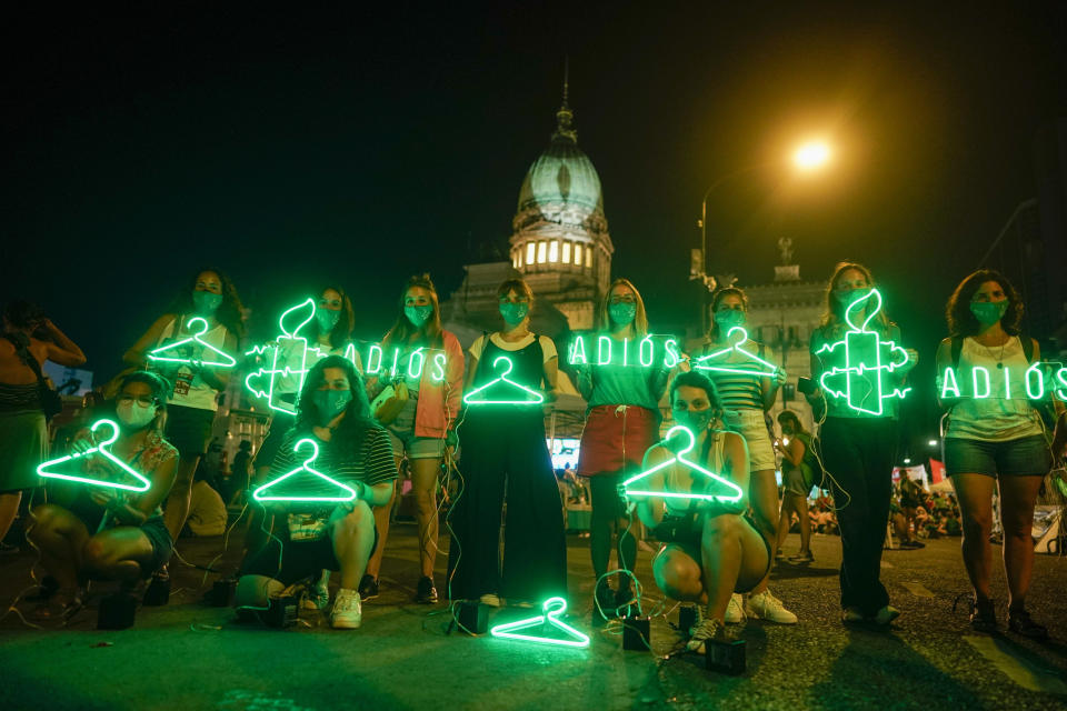 """FILE - In this Dec. 30, 2020 file photo, abortion-rights activists hold hangers, that symbolize illegal abortions, and signs reading in Spanish """"Goodbye"""" after lawmakers approved a bill that legalizes abortion, outside Congress in Buenos Aires, Argentina. (AP Photo/Victor Caivano, File)"""