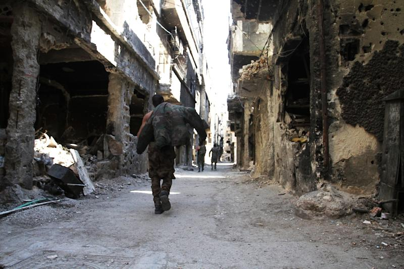 A file picture taken on April 6, 2015 shows men walking past destroyed buildings in the Yarmuk Palestinian refugee camp in Damascus reportedly targeted by the Syrian regime (AFP Photo/YOUSSEF KARWASHAN)