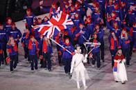 <p>Flag bearer Lizzy Yarnold of Great Britain leads the team, who all wear blue ski jackets, black pants, and red accessories during the opening ceremony of the 2018 PyeongChang Games. (Photo: Ronald Martinez/Getty Images) </p>