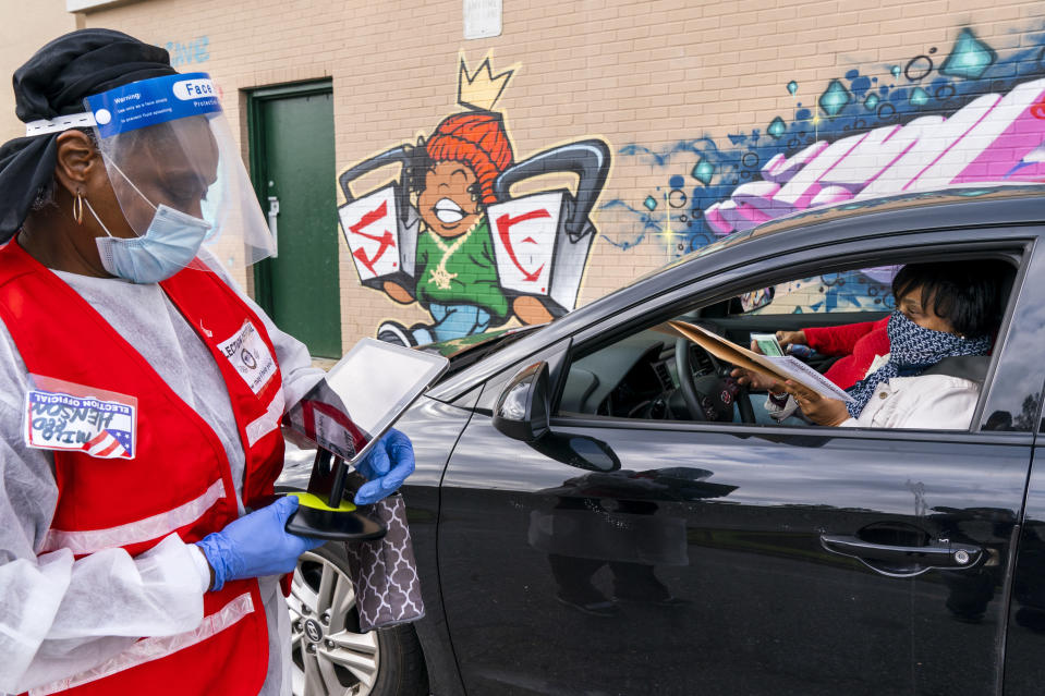 """Poll worker Mildred Henson, left, helps Patria, 57, far right, and Janet Wilson, 68, both of Washington, in car at right of Patria, to submit their ballots from the curbside voting line, Tuesday, Oct. 27, 2020, at Malcolm X Opportunity Center, an early voting center in Washington. Curbside voting is offered at this location for seniors and people with disabilities. """"I voted early because I want to be sure that my health doesn't keep me from voting on the 3rd,"""" says Wilson, """"the primary voting was so crowded that I couldn't vote, so this time I'm voting early."""" (AP Photo/Jacquelyn Martin)"""