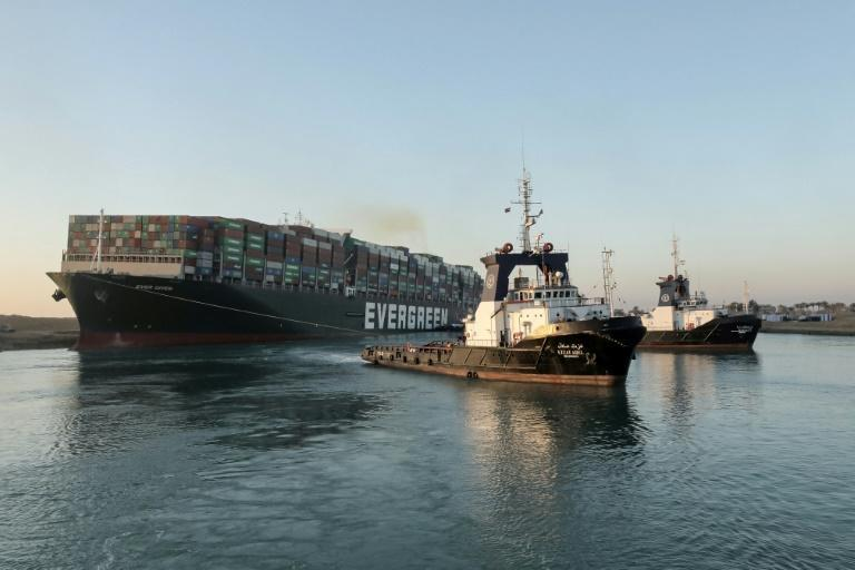 Tugboats pull the Panama-flagged MV Ever Given to unobtrusive sanctuary after its stern and bow were successfully prised from the banks of the Suez Canal