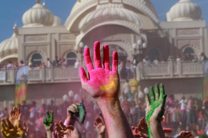 Revelers with colored corn starched hands celebrate during the 2014 Festival of Colors, Holi Celebration at the Krishna Temple Saturday, March 29, 2014, in Spanish Fork, Utah. Nearly 70,000 people are expected to gather starting Saturday at a Sri Sri Radha Krishna Temple in Spanish Fork for the annual two-day festival of colors. Revelers gyrate to music and partake in yoga during the all-day festival, throwing colored corn starch in the air once every hour. The Salt Lake Tribune reports that the large majority of participants are not Hindus, but Mormons. Thousands of students from nearby Brigham Young University come to take part in a festival that is drug and alcohol free. The event stems from a Hindu tradition celebrating the end of winter and the triumph of good over evil. (AP Photo/Rick Bowmer)