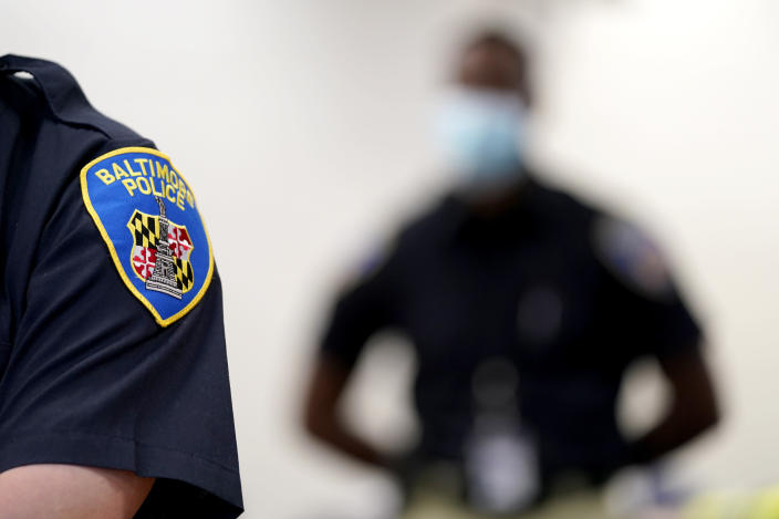 In this Sept. 9, 2020, photo the patch on the shoulder of a Baltimore Police Academy cadet is seen as Ockeive Farquharson, right, listens to a video presentation during a class session focusing on procedural justice in Baltimore. (AP Photo/Julio Cortez)