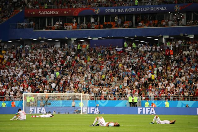<p>The IR Iran players lie dejectedly on the pitch at the end of the 2018 FIFA World Cup Russia group B match between Iran and Portugal at Mordovia Arena on June 25, 2018 in Saransk, Russia. (Photo by Matthew Ashton – AMA/Getty Images) </p>