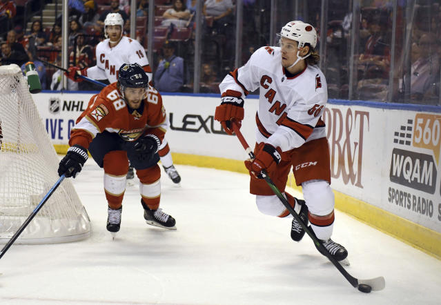 Carolina Hurricanes left wing Erik Haula (56) looks to clear the puck as Florida Panthers center Mike Hoffman (68) follows on the play during the first period of an NHL hockey game Tuesday, Oct. 8, 2019, in Sunrise, Fla. (AP Photo/Jim Rassol)