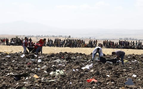 <span>Rescue teams work at the site of the crashed plane, watched by hundreds of bystanders&nbsp;</span> <span>Credit: EWELDE Source:&nbsp; </span>
