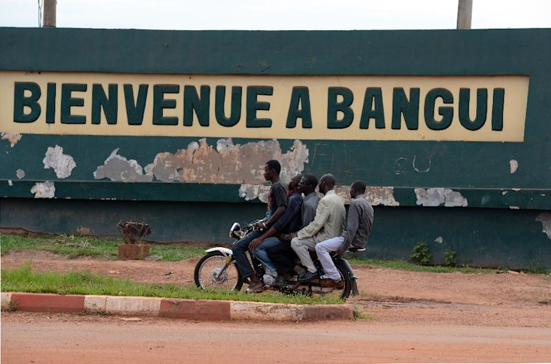 "A motorcycle taxi drives past a sign reading ""Welcome to Bangui"" near the Bangui airport, on May 1, 2014"