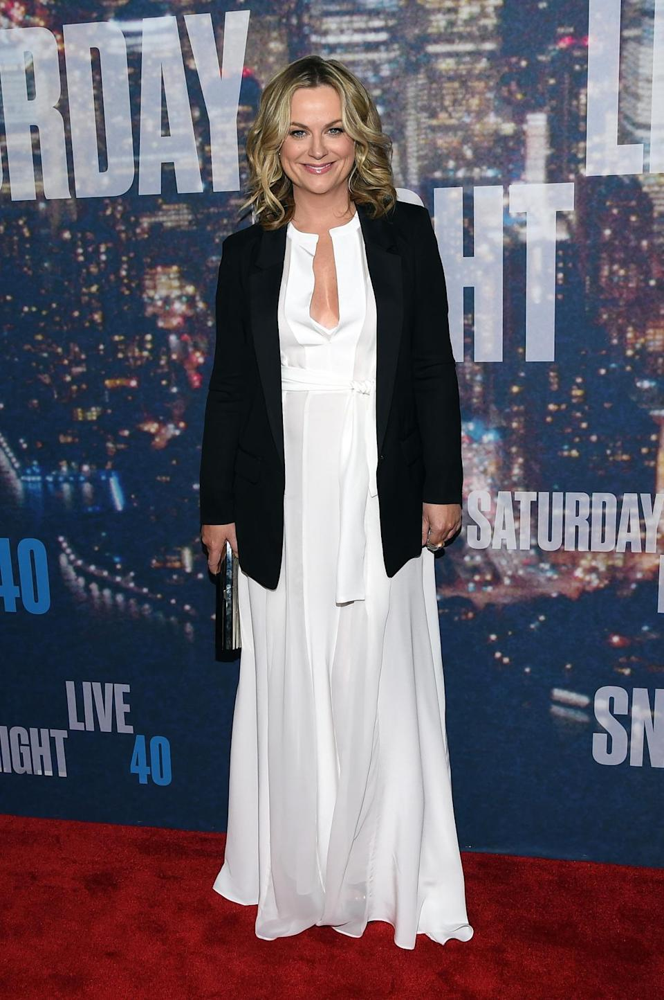 Wearing winter white and covering up with a black blazer, Amy Poehler pulls off the classic color combination.