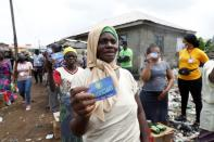 A woman holds her food ticket as people queue for food parcels during distribution by volunteers of the Lagos food bank initiative in a community in Oworoshoki, Lagos