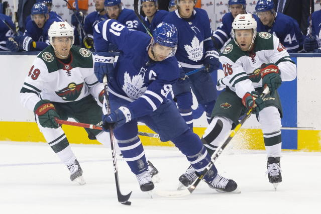 Toronto Maple Leafs' John Tavares (91) brings the puck away from Minnesota Wild's Victor Rask (49) and Gerald Mayhew (26) during the first period of an NHL hockey game Tuesday, Oct. 15, 2019, in Toronto. (Chris Young/The Canadian Press via AP)