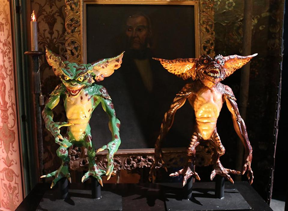 <p>Two of the nasty 'Gremlins' figures strike a pose. Behind them is an eye-less portrait originally used in 'Abbott and Costello Meet Frankenstein.' (Photo: Angela Kim/Yahoo) </p>