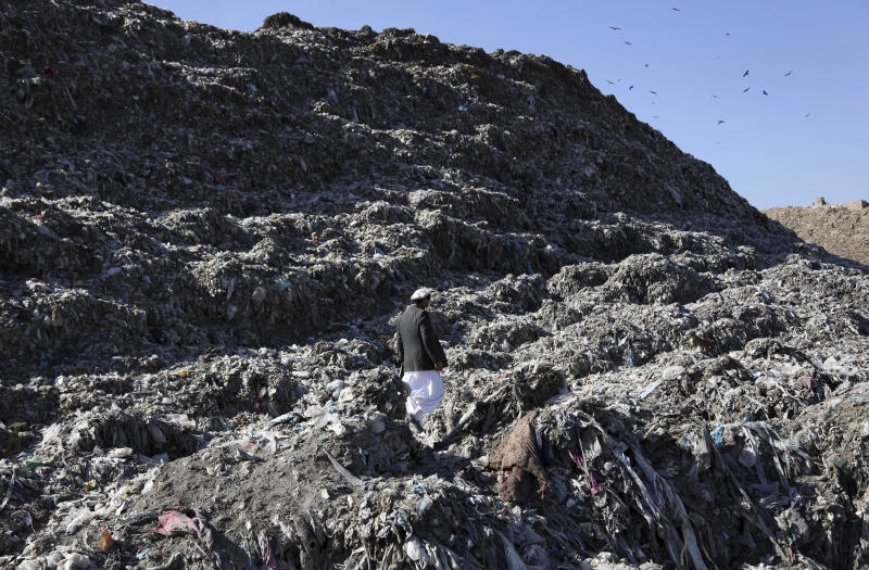In this Oct. 23, 2019 photo, Abdul Basir Akhundzada head of Kabul municipality garbage dump yard, walks at garbage dump yard on the outskirts of Kabul, Afghanistan. Kabul, a city of some 6 million, has become one of the most polluted cities in the world, as decades of war have wrecked infrastructure and caused waves of displaced people. Authorities are trying to tackle pollution in the country's capital, which may be even deadlier than 18-year-old war. (AP Photo/Rahmat Gul)