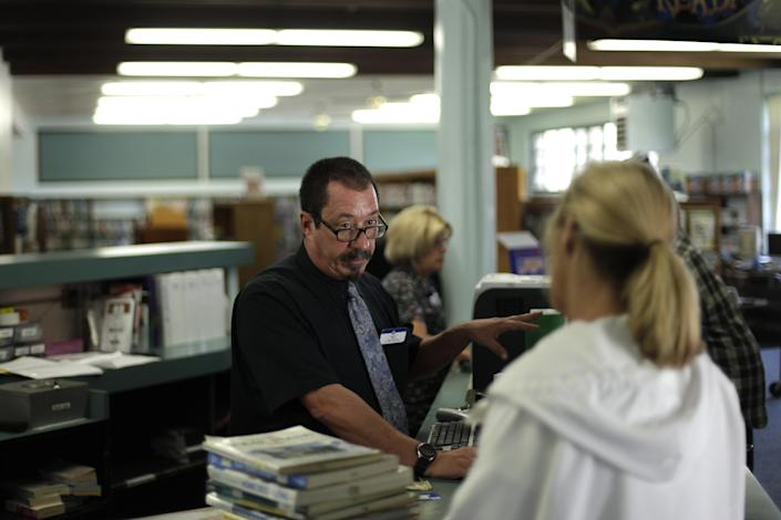 Library Branch Manager Matt Beatty, center, helps a customer at a San Diego Public Library Friday, June 8, 2012, in San Diego. Beatty has worked for the city as a librarian for more than 11 years. Voters in San Diego and San Jose overwhelmingly approved ballot measures last week to roll back municipal retirement benefits - and not just for future hires but for current employees. (AP Photo/Gregory Bull)