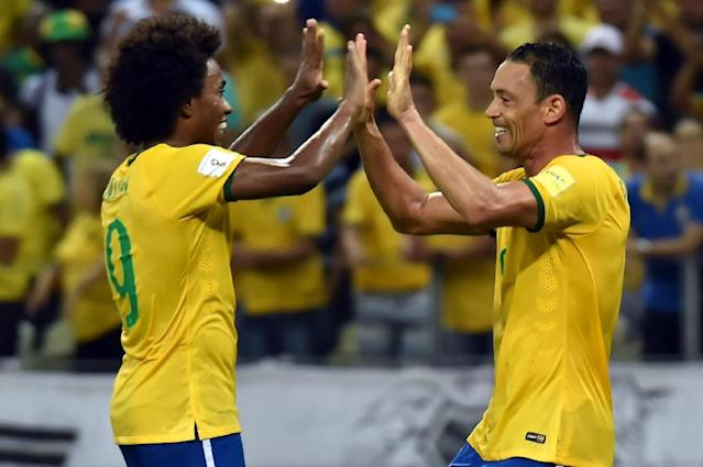 Brazil's Ricardo Oliveira (R) celebrates with teammate Willian after scoring against Venezuela during World Cup South American Qualifiers match in Brazil, on October 13, 2015 (AFP Photo/Nelson Almeida)