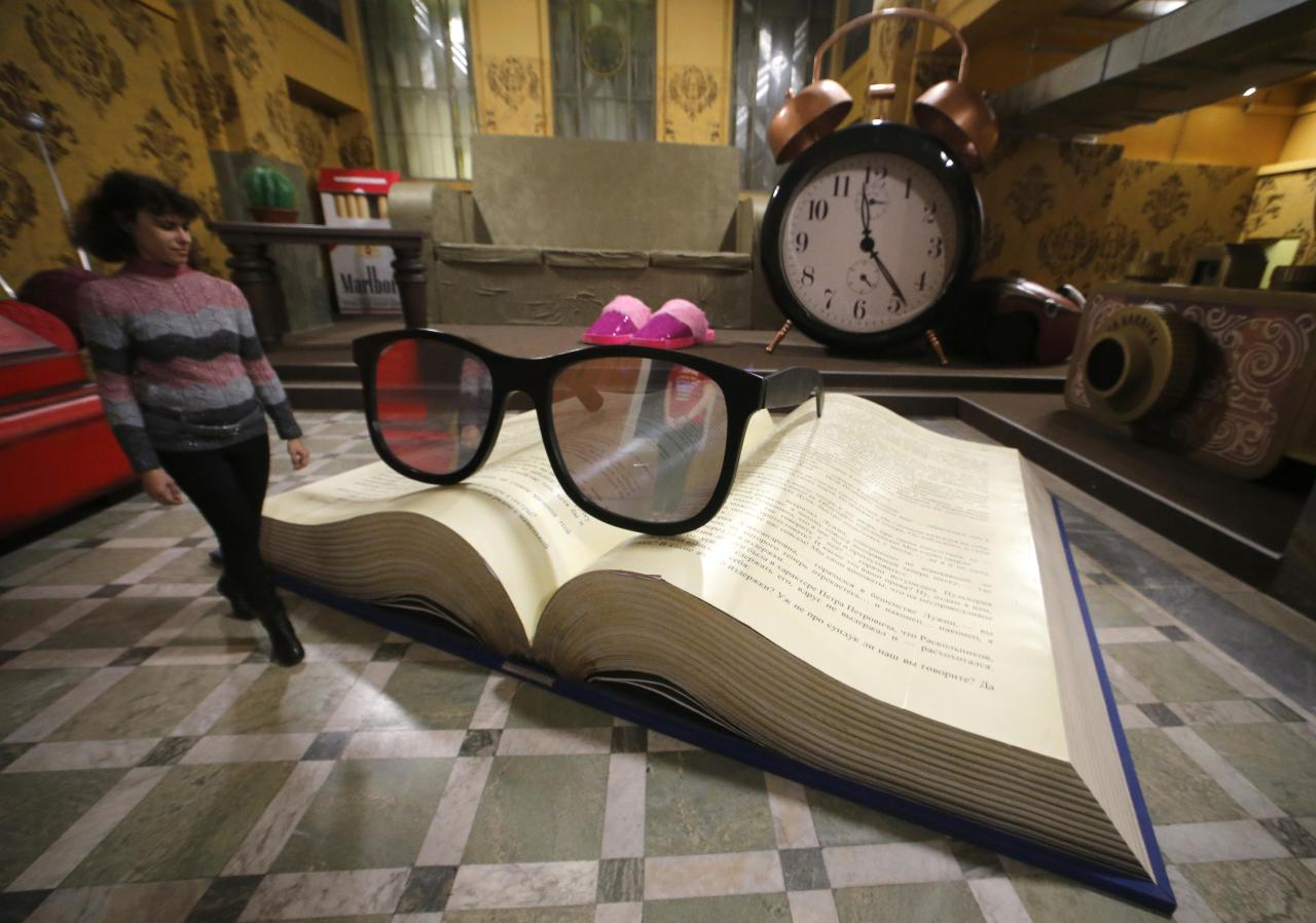A visitor looks at an art installation depicting huge glasses on an opened book, at the Museum of Optical Illusions in St. Petersburg, October 7, 2014. The museum offers visitors a chance to become involved in their 3D installations, according to local media. REUTERS/Alexander Demianchuk (RUSSIA  - Tags: SOCIETY)