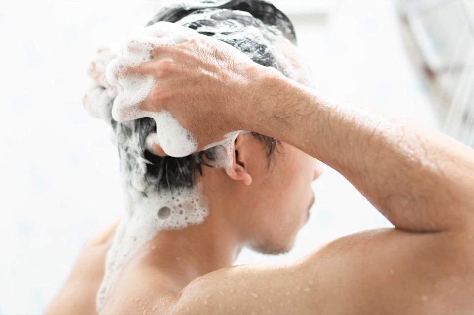 Man washing his hair with shampoo in the shower