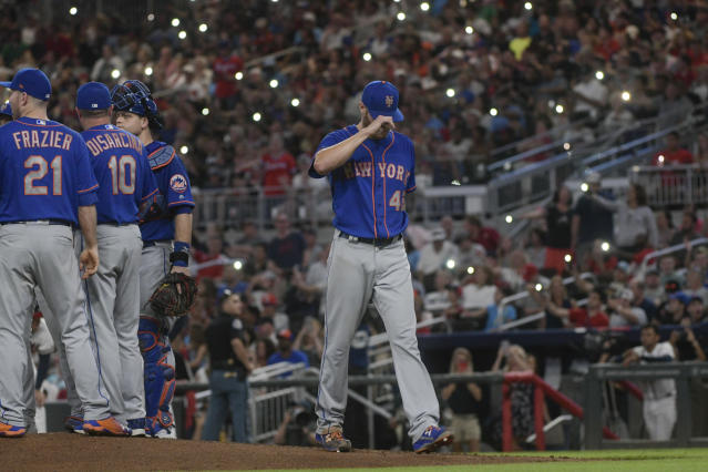 New York Mets pitcher Zack Wheeler leaves the baseball game as Atlanta Braves fans wave cell-phone lights under dimmed stadium lights during the sixth inning of a baseball game Tuesday, June 12, 2018, in Atlanta. (AP Photo/John Amis)