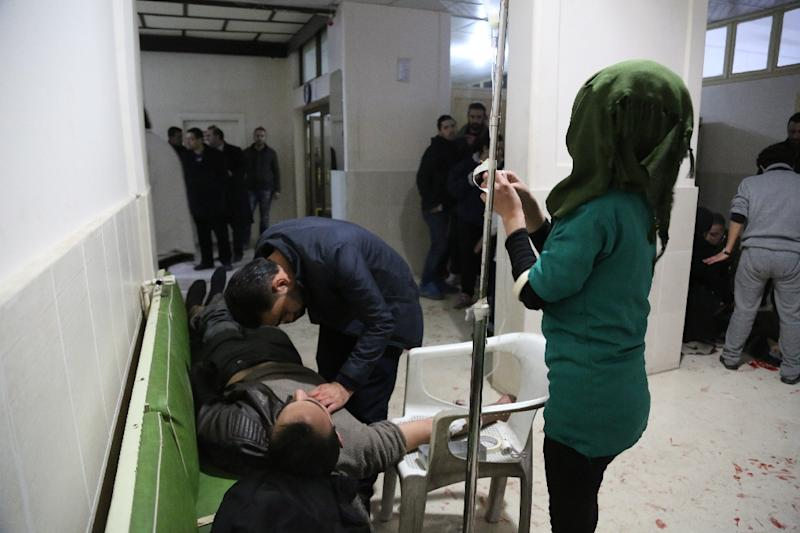 A wounded man receives first aid on December 30, 2015 in Qamishli, after three separate explosions