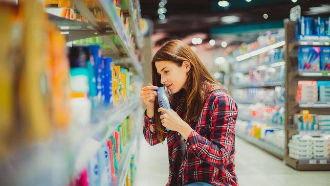 A beautiful young woman comparing two cosmetic products in the drugstore aisle of the grocery store.