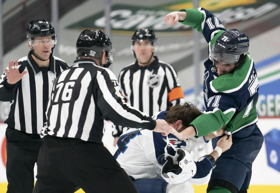 Vancouver Canucks centerZack MacEwen (71) fights with Winnipeg Jets defenseman Derek Forbort (24) during first-period NHL hockey game action in Vancouver, British Columbia, Sunday, Feb. 21, 2021. (Jonathan Hayward/The Canadian Press via AP)
