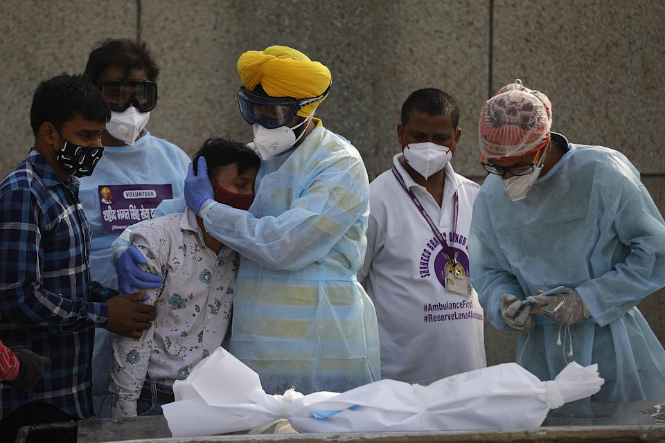 A man mourns as he and volunteers prepare for the last rites of a child who died due to the novel coronavirus