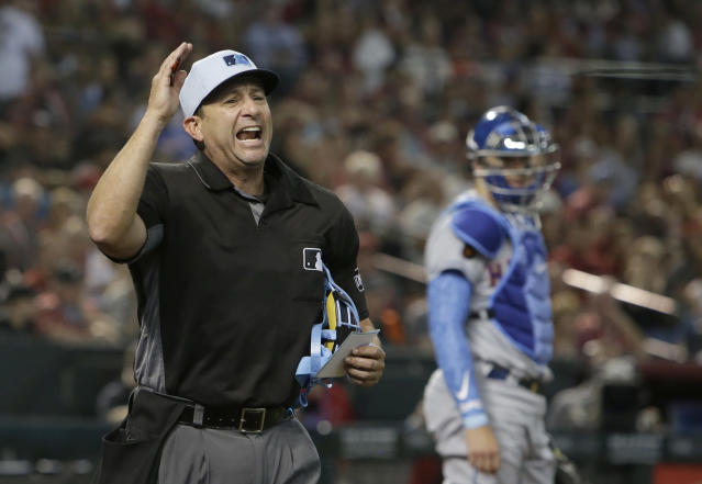 MLB umpire Jim Reynolds, left, ejects New York Mets relief pitcher Jason Vargas in the fourth inning during a baseball game against the Arizona Diamondbacks, Sunday, June 17, 2018, in Phoenix. Vargas was on the bench and not in the game. (AP Photo/Rick Scuteri)