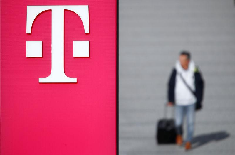 FILE PHOTO: A man walks past the logo of Deutsche Telekom AG at the headquarters of German telecommunications giant in Bonn