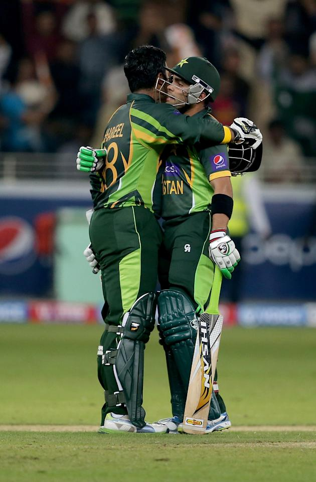 DUBAI, UNITED ARAB EMIRATES - DECEMBER 13:   Umar Akmal (R) congratulate Sharjeel Khan (L) during the second Twenty20 International match between Pakistan and Sri Lanka at Dubai Sports City Cricket Stadium on December 13, 2013 in Dubai, United Arab Emirates.  (Photo by Francois Nel/Getty Images)