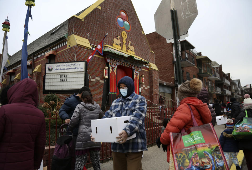 People receive free food from the United Sherpa Association's weekly food pantry on Friday, Jan. 15, 2021, in the Queens borough of New York. The pantry began in April with a focus on the Nepalese community, international students and families living in the country without permission. (AP Photo/Jessie Wardarski)