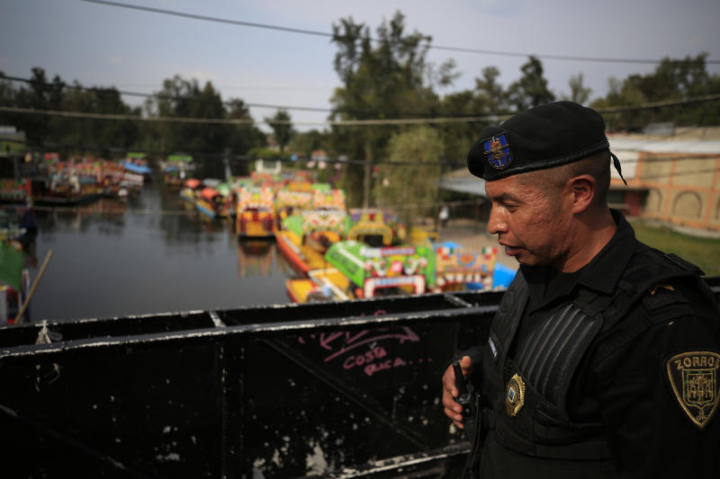 A police officer patrols on a bridge over a canal filled with scores of parked and a handful of occupied trajineras, the colorful passenger boats typically rented by tourists, families, and groups of young people, in Xochimilco, Mexico City, Friday, Sept. 6, 2019. The usually festive Nativitas pier was subdued and largely empty Friday afternoon, with some boat operators and vendors estimating that business was down by 80% on the first weekend following the drowning death of a youth that was captured on cellphone video and seen widely in Mexico. Borough officials stood on the pier to inform visitors of new regulations that went into effect Friday limiting the consumption of alcohol, prohibiting the use of speakers and instructing visitors to remain seated.(AP Photo/Rebecca Blackwell)