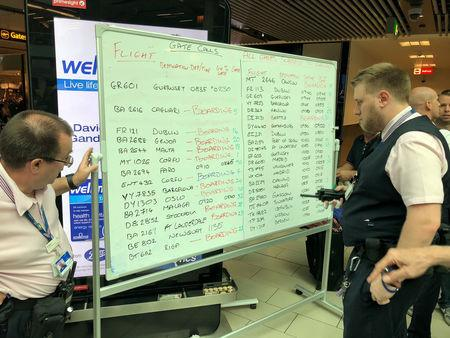 Airport staff write on a white board as Gatwick, Britain's second busiest airport, was forced to post flight information on white boards after an IT glitch meant its digital screens failed in Gatwick, London, Britain, August 20, 2018 in this picture obtained from social media. TWITTER/ @EVDB /via REUTERS