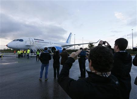 Bombardier employees and guests take photos of the CSeries aircraft prior to its first test flight in Mirabel, Quebec, September 16, 2013. REUTERS/Christinne Muschi