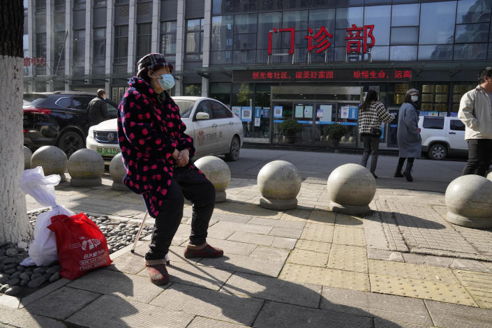 A resident wearing a mask sits outside the clinic entrance of the Hubei Provincial Hospital of Integrated Chinese and Western Medicine also known as the Hubei Province Xinhua Hospital where a World Health Organization team of researchers arrive on its first field trip in Wuhan in central China's Hubei province on Friday, Jan. 29, 2021. The World Health Organization team of researchers emerged from their hotel Thursday for the first time since their arrival in the central Chinese city of Wuhan to start searching for clues into the origins of the COVID-19 pandemic. (AP Photo/Ng Han Guan)
