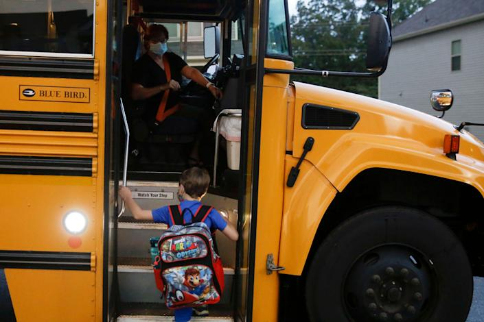 Paul Adamus, 7, climbs the stairs of a bus before the fist day of school on Monday, Aug. 3, 2020, in Dallas, Ga. (AP Photo/Brynn Anderson) (Photo: ASSOCIATED PRESS)