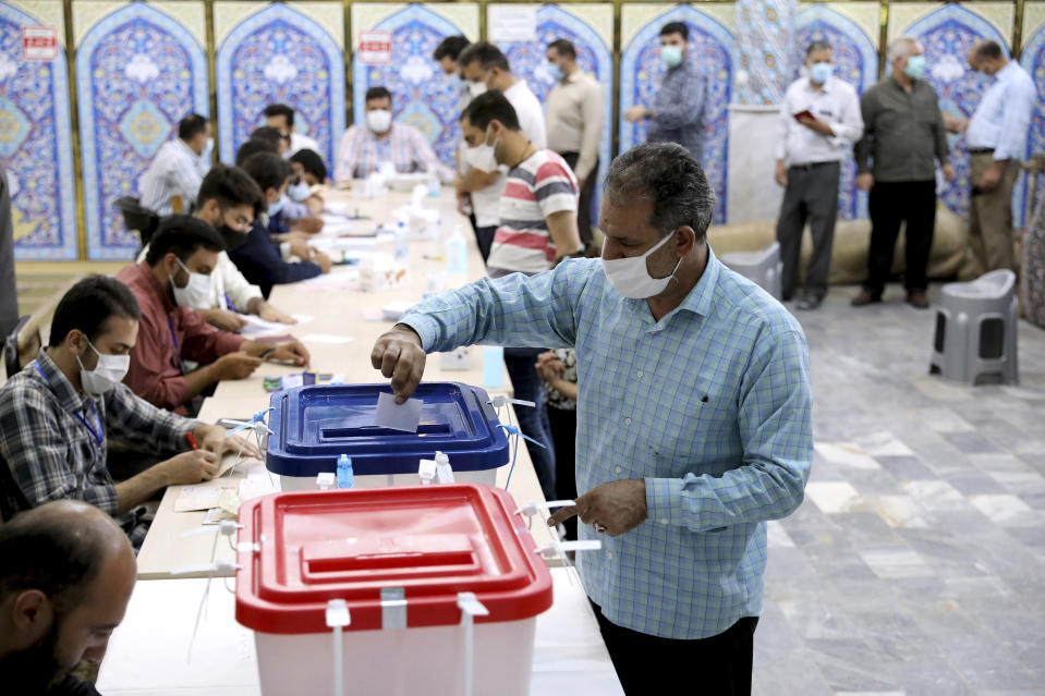 A voter casts his ballot for the presidential election at a polling station in Tehran, Iran, Friday, June 18, 2021. Iranians voted Friday in a presidential election that a hard-line protege of Supreme Leader Ayatollah Ali Khamenei seemed likely to win, leading to low turnout fueled by apathy and calls for a boycott. (AP Photo/Ebrahim Noroozi)