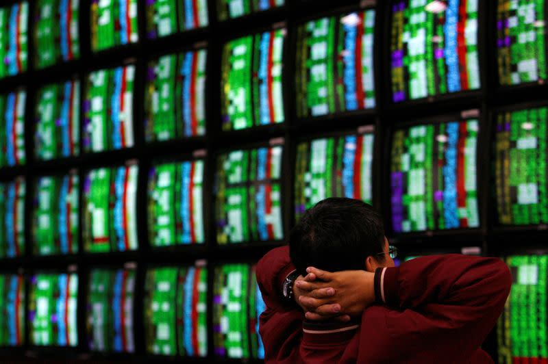 FILE PHOTO: A man looks at stock market monitors in Taiwan