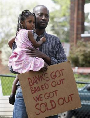 "Saidov Wane and his two-year-old daughter Khady protest against home foreclosures in the East Price Hill neighborhood during a Occupy Cincinnati march in Cincinnati, Ohio, March 24, 2012. Occupy activists across America say they have found a cause that represents an issue for the ""99 percent"" and embodies the movement's anti-Wall Street message: helping struggling homeowners fight foreclosure and eviction. Picture taken March 24, 2012."