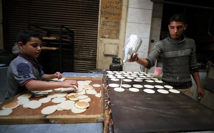 On Wednesday, a baker in Egypt preparing a snack for Ramadan called Qatayef spills the dough while his young aide handles an earlier batch.