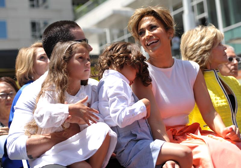 Actress and singer Jennifer Lopez, right, appears with her twins Emme Marbiel Muniz, left, and Maximilian David Muniz, on the lap of Casper Smart at a ceremony honoring her on the Hollywood Walk of Fame on Thursday, June 20, 2013 in Los Angeles. (Photo by John Shearer/Invision/AP)
