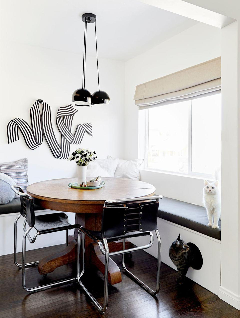 """<p>Take note from this dining nook by <a href=""""https://stylebyemilyhenderson.com/blog/moto-reveal-emily-bowsers-bright-dining-nook-custom-cat-friendly-banquette-duh"""" rel=""""nofollow noopener"""" target=""""_blank"""" data-ylk=""""slk:Emily Henderson"""" class=""""link rapid-noclick-resp"""">Emily Henderson</a> and design with your furry friends in mind. This custom banquette features a little doorway for the occupants cats. Though it was initially going to contain extra storage space, they decided a """"kitty cave"""" was a lot more fun. The top folds up when you remove the cushion just in case the cats need help finding another exit. </p>"""