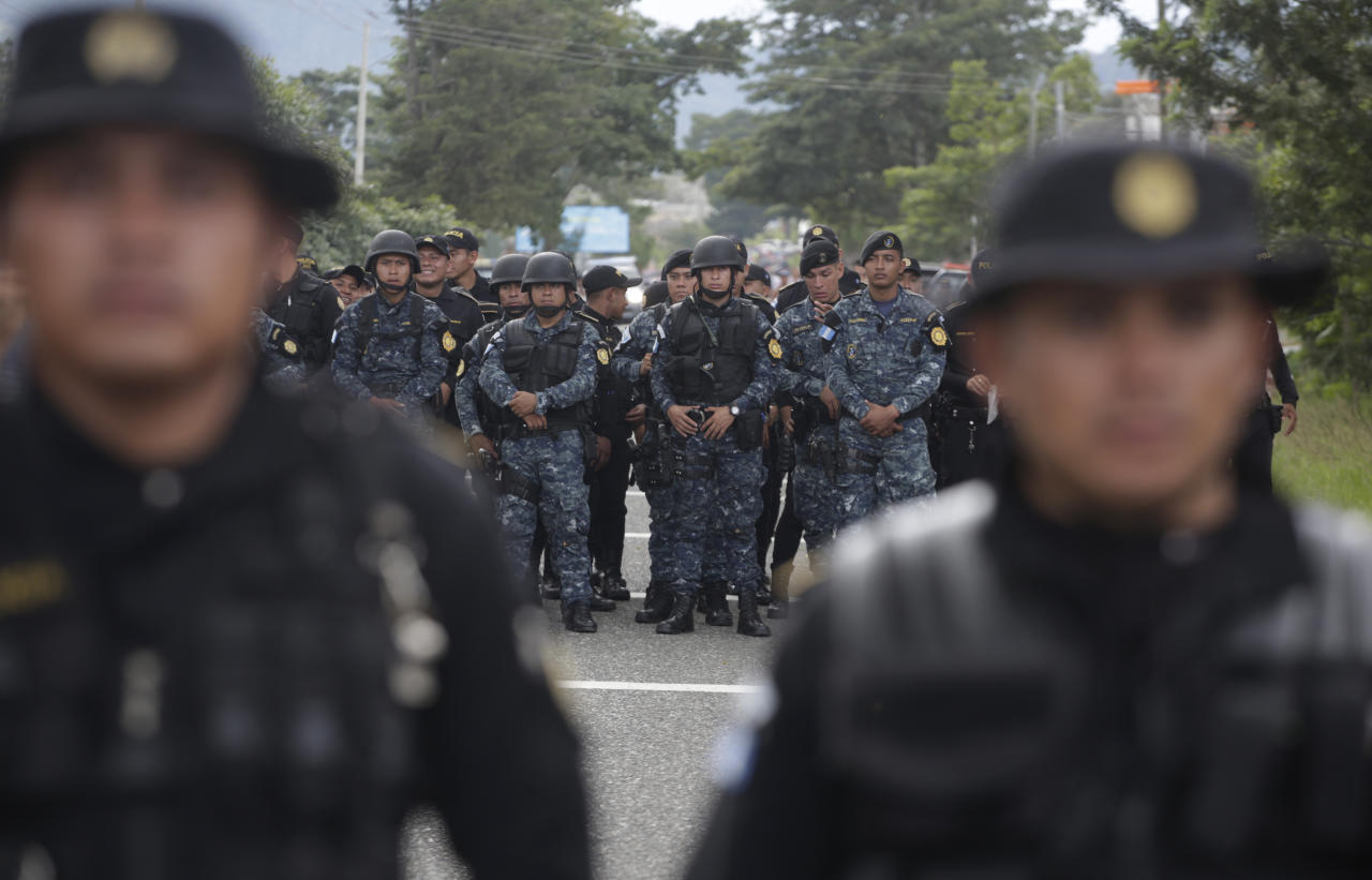 Guatemalan police stand in the road to block Honduran migrants making their way to the U.S., in Esquipulas, Guatemala, Monday, Oct. 15, 2018. The caravan began as about 160 people who first gathered early Friday to depart from San Pedro Sula, Honduras, figuring that traveling as a group would make them less vulnerable to robbery, assault and other dangers common on the migratory path through Central America and Mexico. The group has since grown to at least 1,600 people. (AP Photo/Moises Castillo)