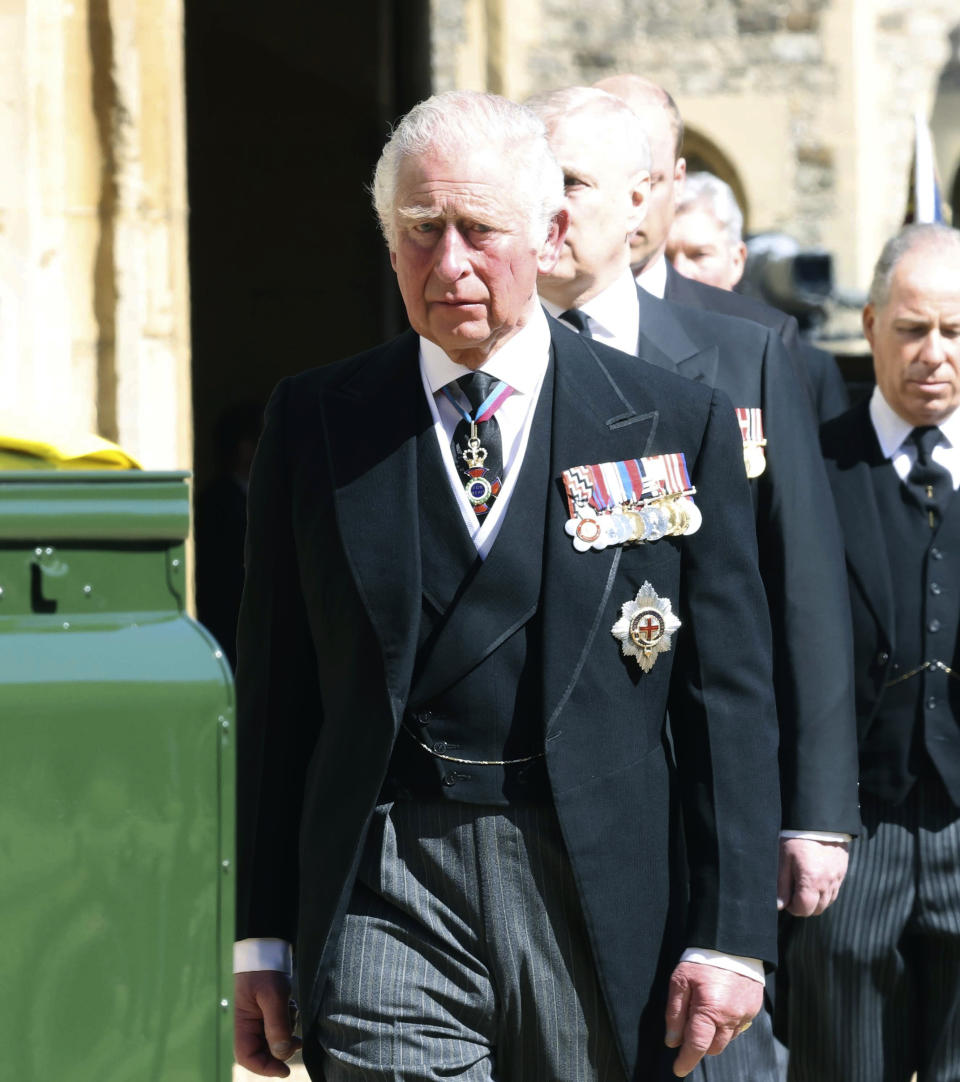 Prince Charles walks behind the Land Rover Defender carrying the Duke of Edinburgh's coffin ahead of his funeral at Windsor Castle, in Windsor, England, Saturday April 17, 2021. Prince Philip died April 9 at the age of 99 after 73 years of marriage to Britain's Queen Elizabeth II. (Ian Vogler/Pool via AP)