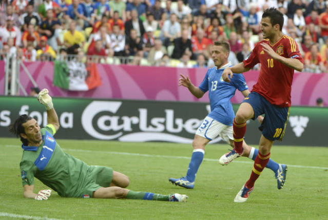 Spanish midfielder Cesc Fabregas (R) scores against Italian goalkeeper Gianluigi Buffon during the Euro 2012 championships football match Spain vs Italy on June 10, 2012 at the Gdansk Arena. AFP PHOTO / PIERRE-PHILIPPE MARCOUPIERRE-PHILIPPE MARCOU/AFP/GettyImages